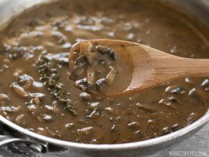 a wooden spoon over a saucepan of mushroom gravy for a vegetarian Thanksgiving