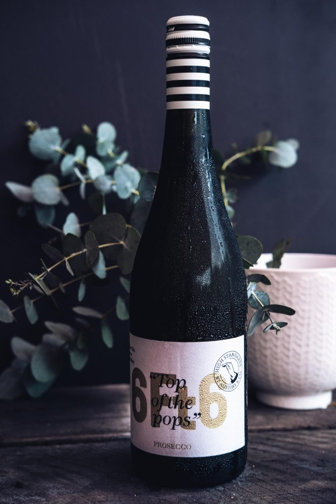wine bottle in front of eucalyptus leaves