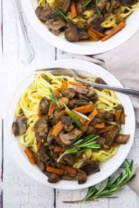 plate of mushroom bourguignon with pasta and a fork