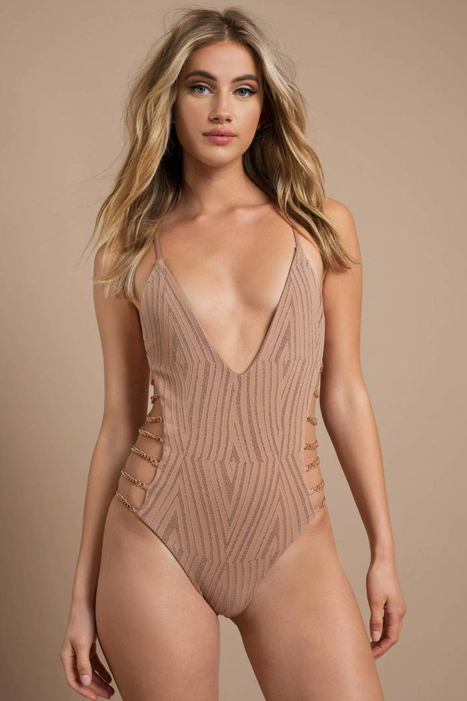 A woman in a blush one piece swimwear with chain details on the side